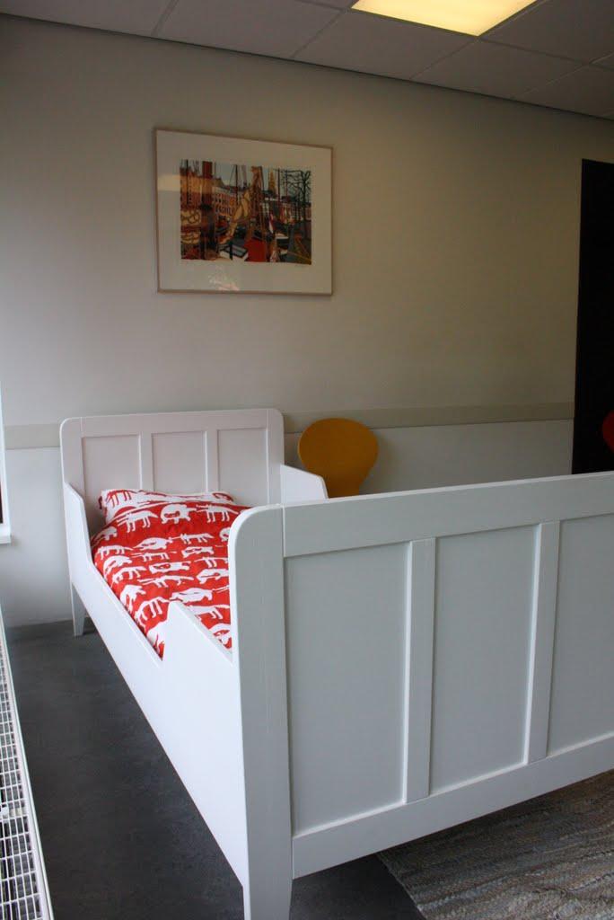 Eenpersoons bed met panelen.